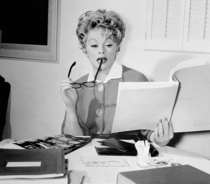 Actress Lucille Ball seated behind a desk and reading a brochure